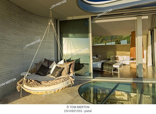 Hanging cushion bed on sunny modern luxury home showcase patio