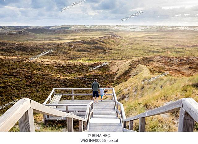 Back view of father and little daughter standing on viewing platform looking at landscape, Sylt, Germany