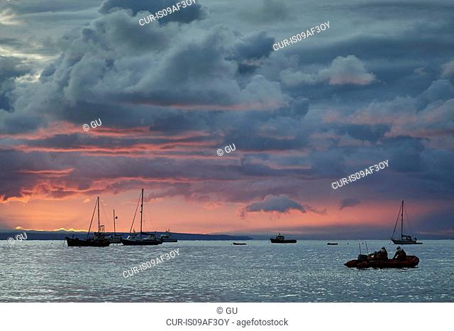 Boats silhouetted at sunrise, Tenby, Wales, UK