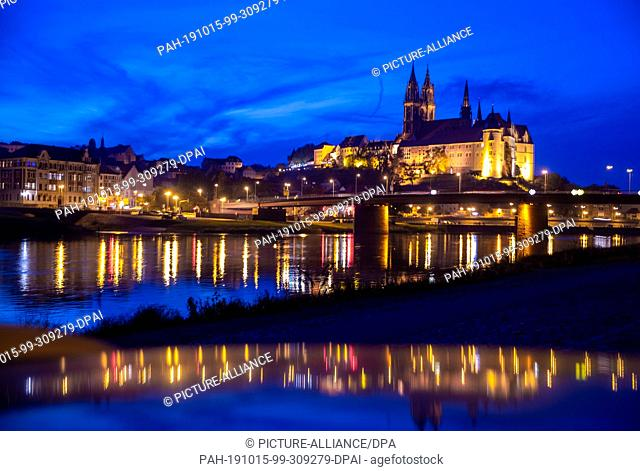 15 October 2019, Saxony, Meißen: The illuminated Albrechtsburg castle and the cathedral of Meissen are reflected in the evening in the Elbe