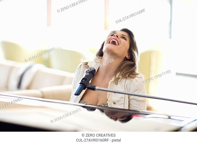 Woman singing and playing piano