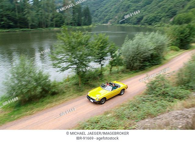 Yellow vintage car MG driving along a river
