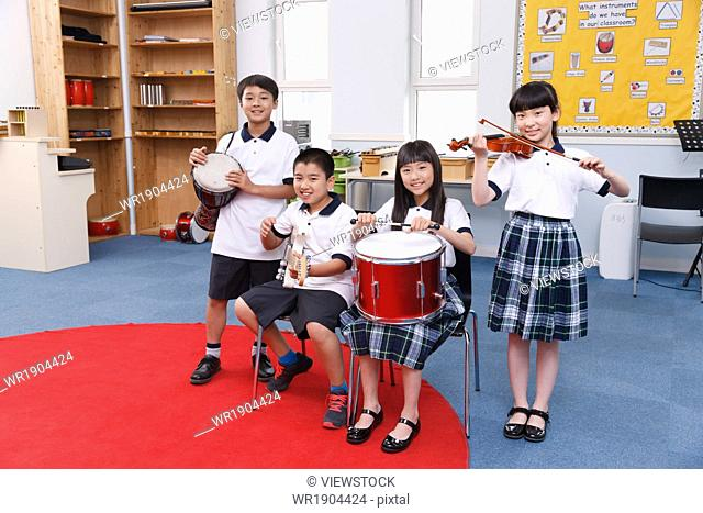 Four students are playing musical instruments
