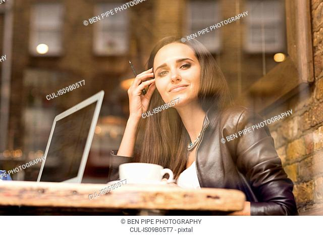 Window view portrait of young businesswoman with laptop in cafe
