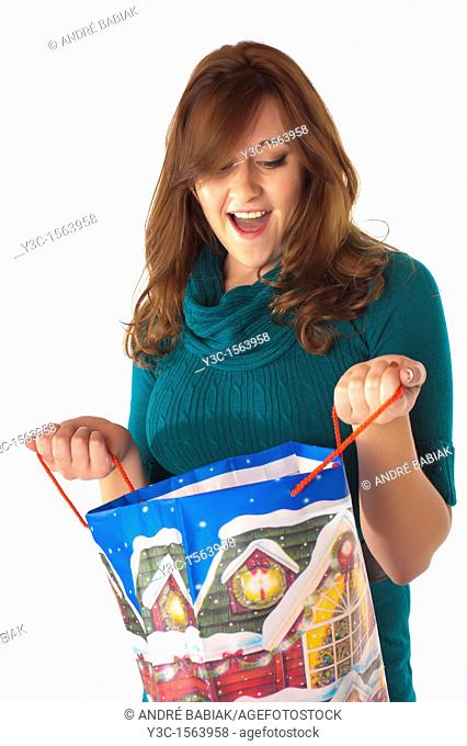 Attractive woman looks happily surprised while looking into Christmas themed shopping bag