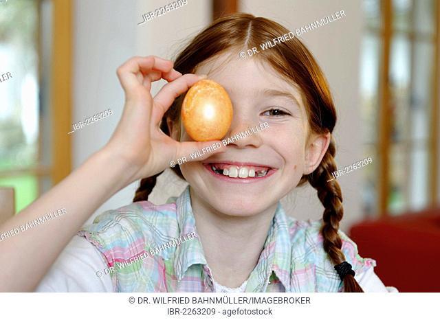 Child, girl holding a coloured Easter egg