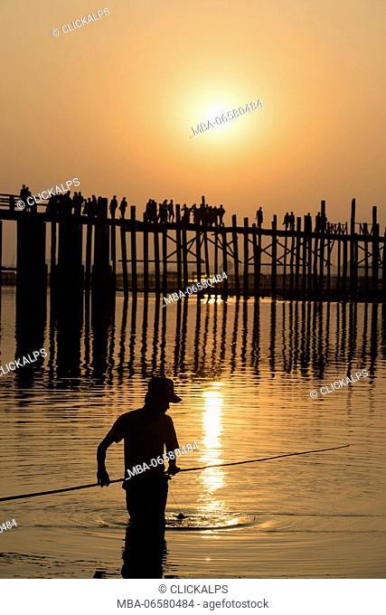 Amarapura, Mandalay region, Myanmar, Man fishing at sunset in front of the U Bein bridge