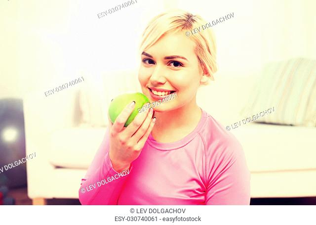 healthy eating, organic food, diet and people concept - happy woman eating apple at home
