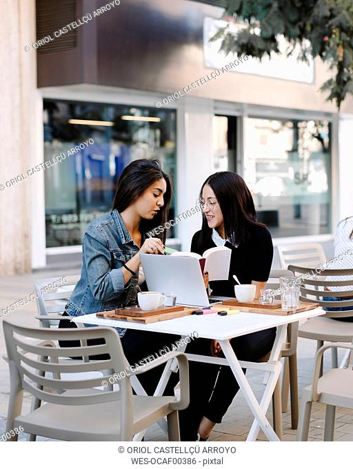 Two friends sitting together at a pavement cafe with book and laptop