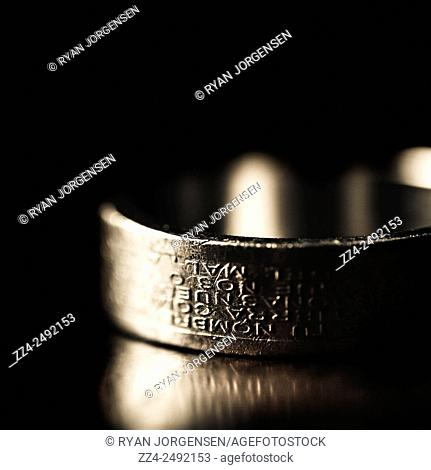Worn and weathered mens silver ring lay abandoned on a reflective wooden surface after the passing of nobility. Heirloom to the throne