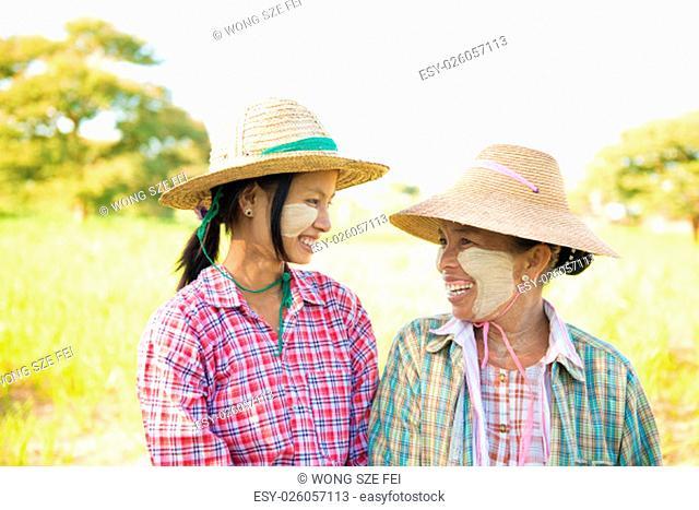 Portrait of a Myanmar female farmer with thanaka powdered face at farmland