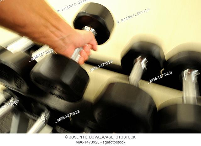 Male lifting dumbell, motion