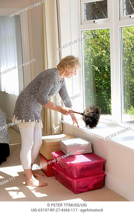 House Move; Woman using an Ostrich feather duster to dust her home
