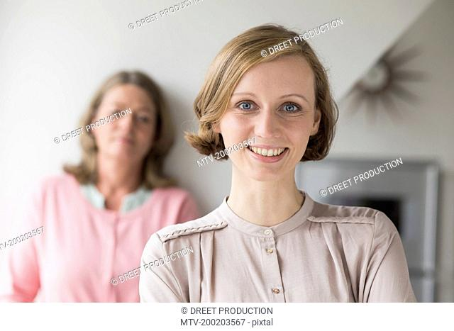 Smiling adult daughter with mother in background, portrait