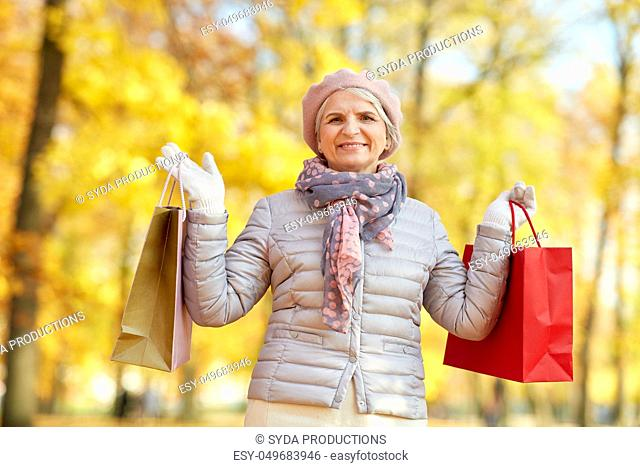 senior woman with shopping bags at autumn park
