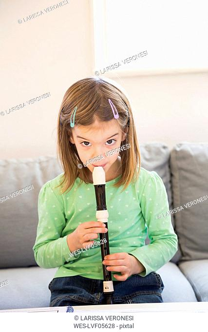 Portrait of little girl sitting on couch with recorder