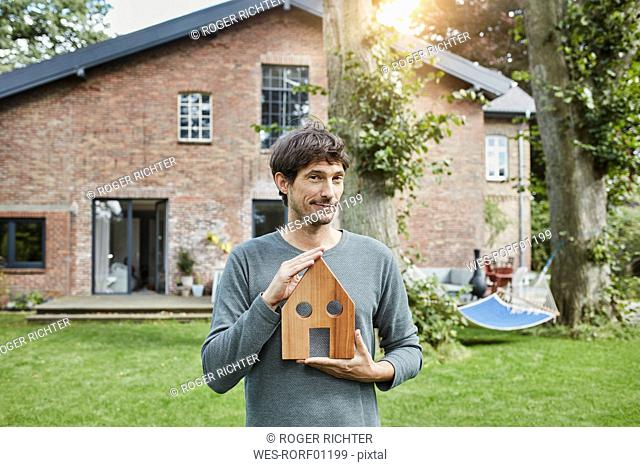 Portrait of man in garden of his home holding house model