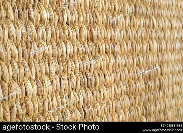 Meshwork of woven reed wicker texture background. Angular view