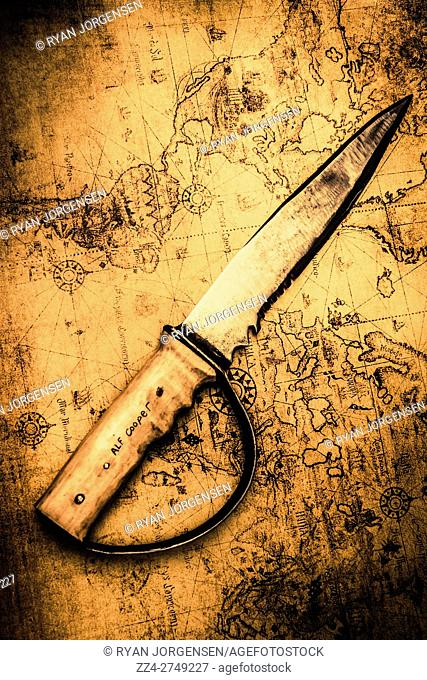 Historic nautical photo on a vintage pirate sword on old world sailing map. Plot and strategize global domination
