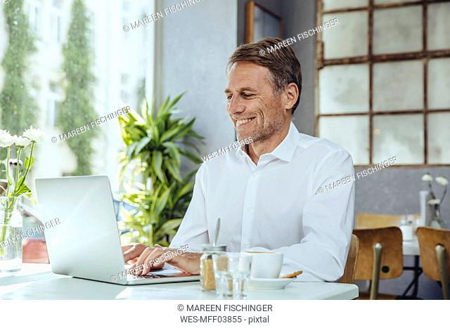 Smiling businessman working in cafe with laptop