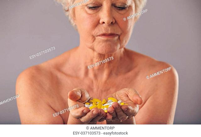 Closeup image of a mature woman holding pills in her hand against grey background. Medication for long life