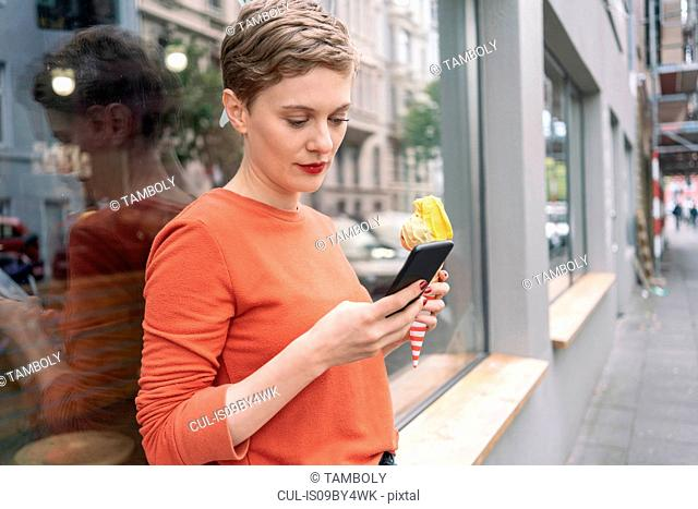 Woman holding ice cream and using smartphone in front of shop, Cologne, Nordrhein-Westfalen, Germany