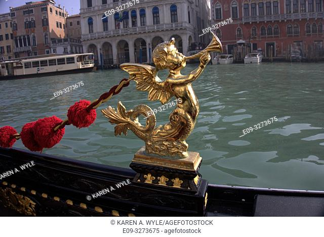details - brass mer-Cupid blowing horn, red-tufted rope - of gondola on Grand Canal in Venice, Italy