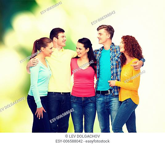 friendship, ecology and people concept - group of smiling teenagers standing and hugging over green background
