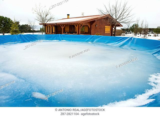 Frozen pool and wooden house in winter. Almansa. Albacete province. Spain