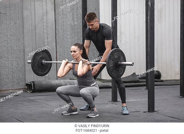 Male instructor assisting young woman crossfit training at gym