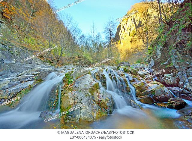 Waterfall in the forest in autumn time