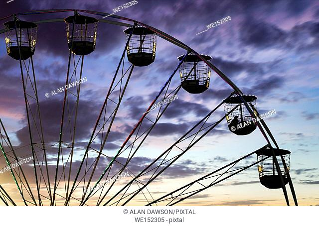 One person on ferris wheel ride at fairground in England. UK