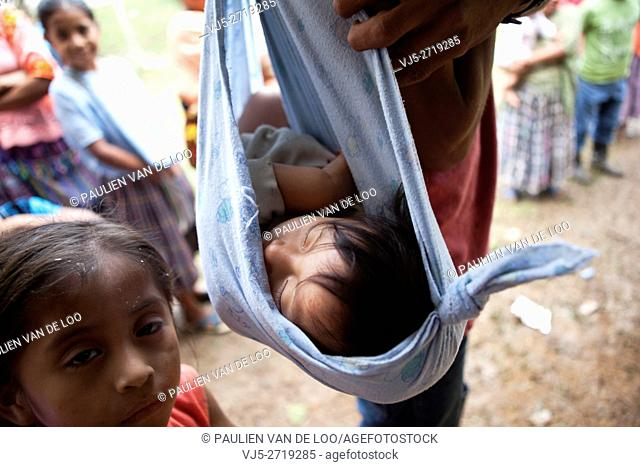 Chahal, Guatemala, a child from a Maya tribe in the jungle is being carried in cloth by her father. Her sister is watching