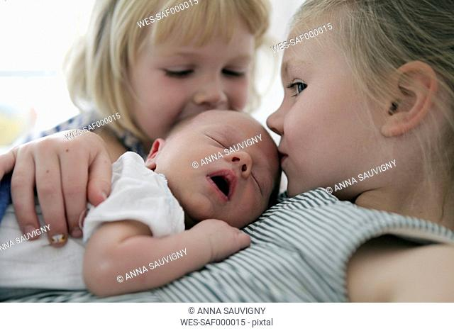 Two little girls kissing their newborn brother