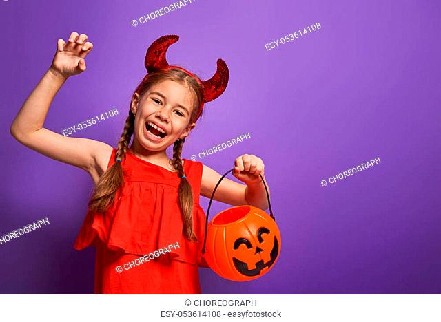 Happy Halloween! Cute little devil with a pumpkin