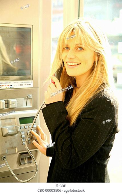 Portrait of Young Woman Using a PAyphone