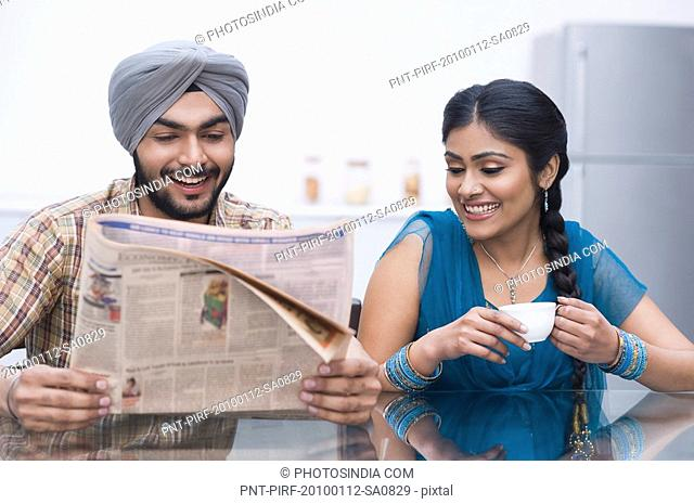 Couple reading a newspaper and smiling