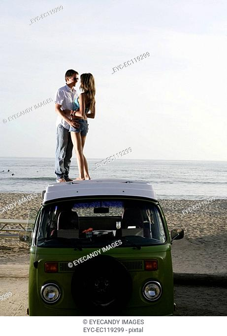 Romantic couple on roof of car