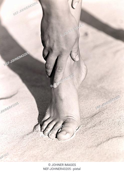 Closeup of foot and hand standing in the sand