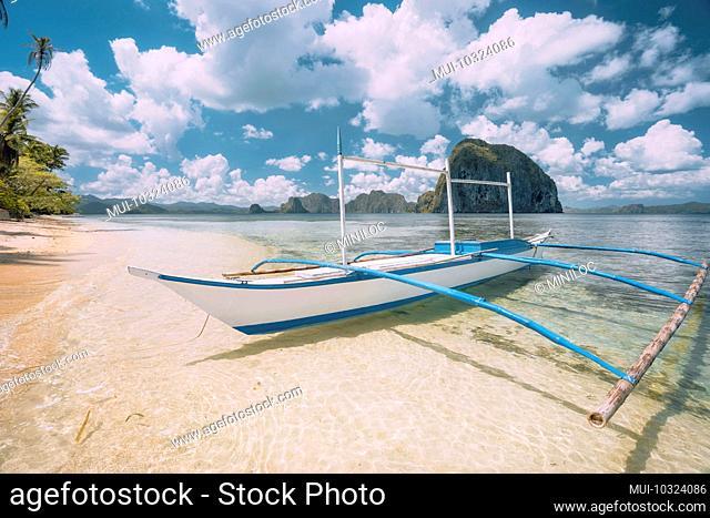 El Nido, Palawan, Philippines, Banca boat on sandy beach in shallow crystal clear water, Pinagbuyutan island in the background