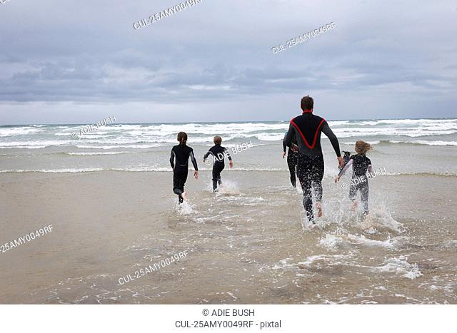 Family running in to the sea in wetsuits