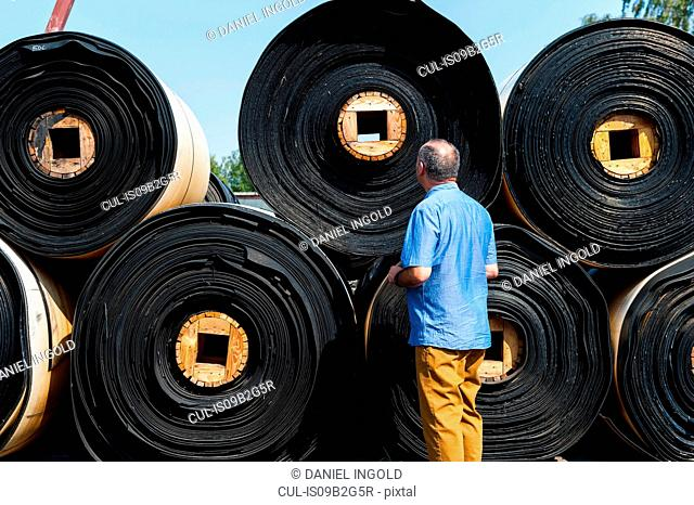 Man looking at rolls of material in yard of castor wheel production factory, Ballenstedt, Germany