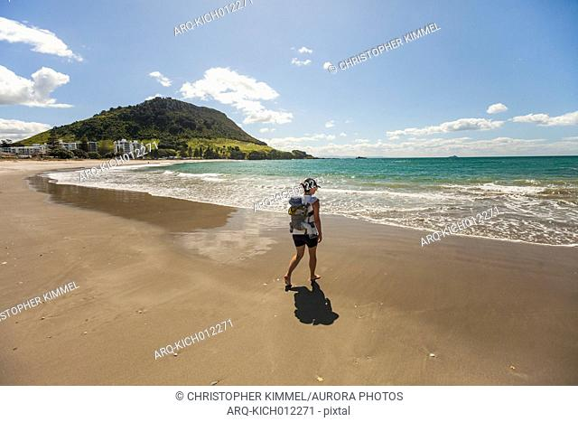 Mother walking with on coastal beach with baby in backpack carrier, New Zealand