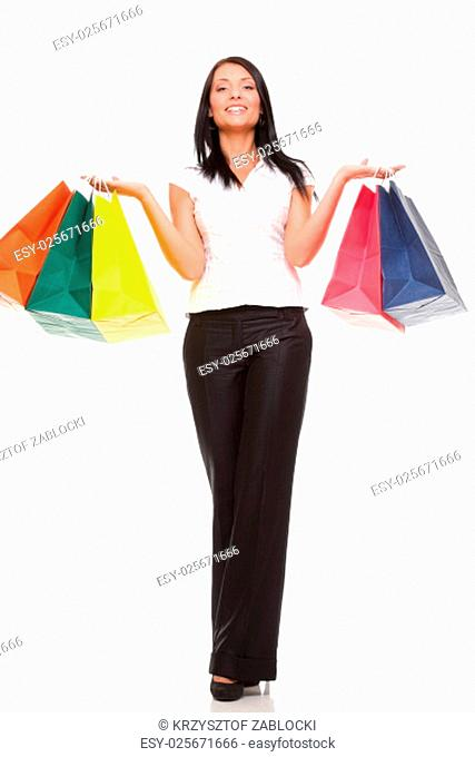 portrait of a young woman carrying shopping bags against white background