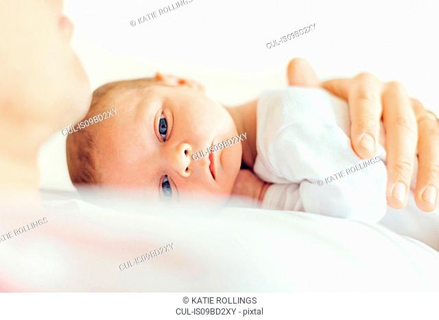 Baby boy lying down on fathers chest looking at camera