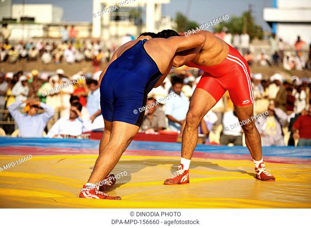 Two wrestlers from India & Pakistan during friendly wrestling match ; cultural events for 300th year's celebrations of Consecration of perpetual Sikh Guru...