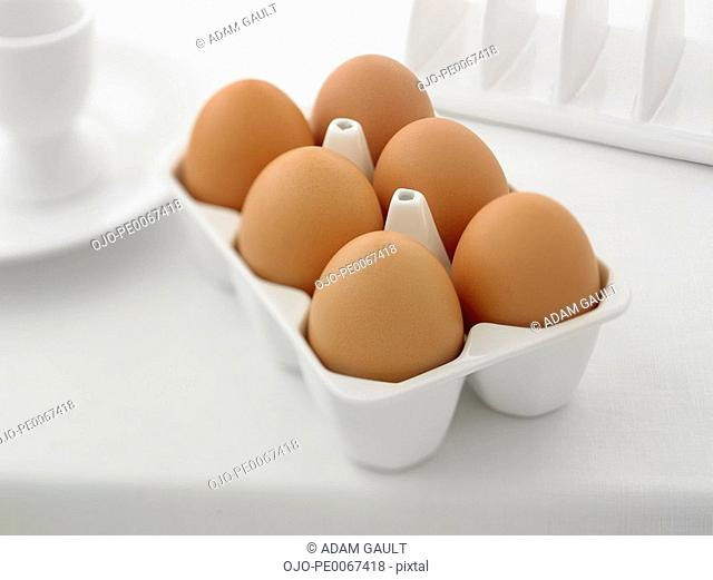 Close up six eggs in carton