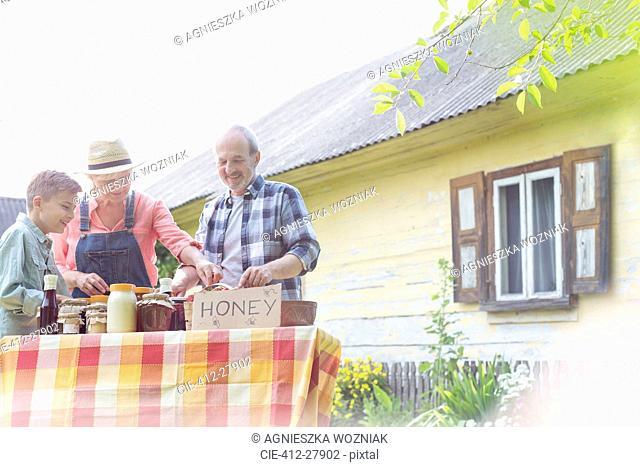 Grandparents and grandson selling honey