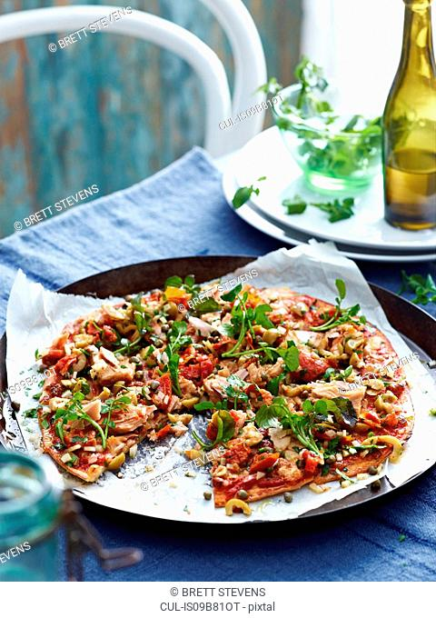 Tuna and green olive pizza in pizza dish, close-up