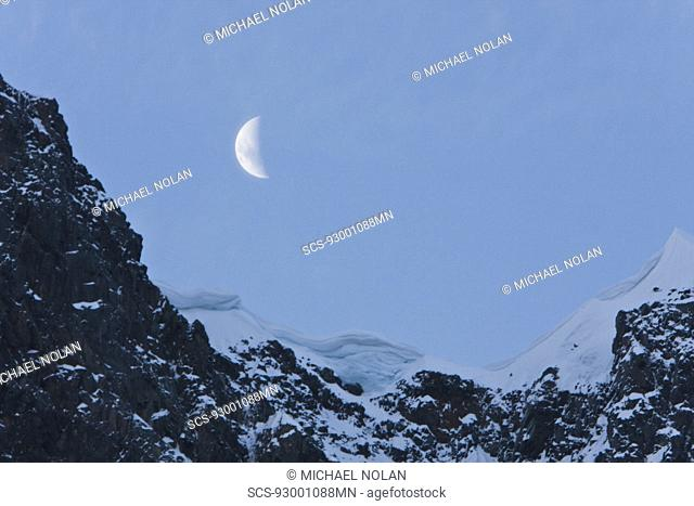 A waxing moon showing over snow covered cliffs in the Lemaire Channel on the west side of the Antarctic peninsula